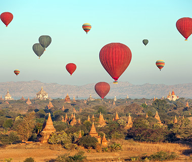 Multicolored hot air balloons over Buddhist temples at sunrise. Bagan, Myanmar.